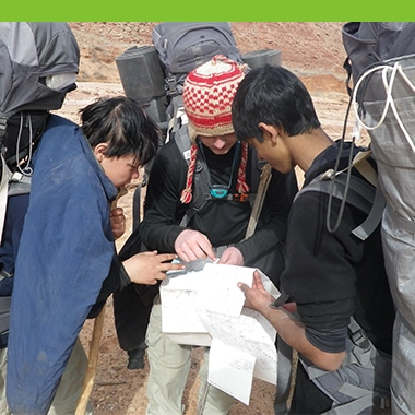 Aspiro students reading a map whilst backpacking