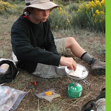 Aspiro student cooking in the wilderness using a gas burner