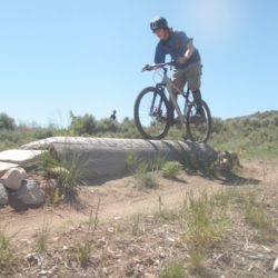 Aspiro student riding mountain bike carefully along log