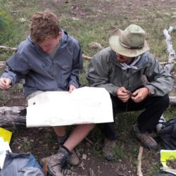 Aspiro students reading a map in the wilderness