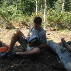 Aspiro student writing in diary in the wilderness