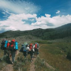 Aspiro students backpacking through green wilderness