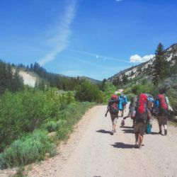 Aspiro students backpacking on dirt road