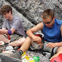 Aspiro students preparing a meal on rocks
